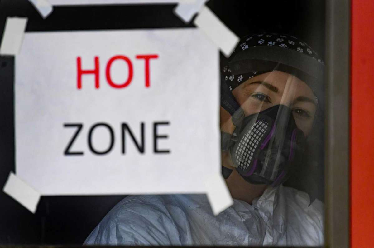 Person dressed in health PPE behind hot zone sign